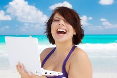 Woman with laptop computer on the beach Stock Images