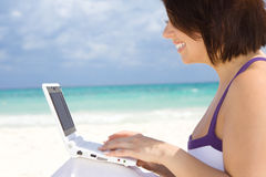 Woman with laptop computer on the beach. Lovely woman with laptop computer on the beach Stock Photos