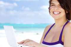 Woman with laptop computer on the beach. Lovely woman with laptop computer on the beach Royalty Free Stock Images