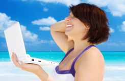 Woman with laptop computer on the beach Stock Photography