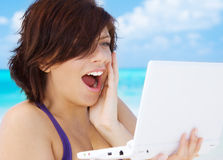 Woman with laptop computer on the beach. Lovely woman with laptop computer on the beach Stock Image