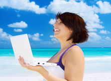 Woman with laptop computer on the beach Royalty Free Stock Images