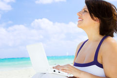 Woman with laptop computer on the beach Royalty Free Stock Image