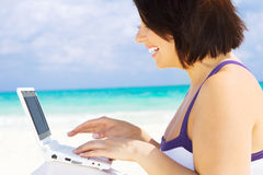 Woman with laptop computer on the beach. Lovely woman with laptop computer on the beach Royalty Free Stock Photography