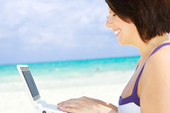 Woman with laptop computer on the beach. Lovely woman with laptop computer on the beach Stock Photo