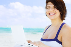 Woman with laptop computer on the beach. Lovely woman with laptop computer on the beach Royalty Free Stock Photo