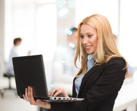 Woman with laptop computer in office Stock Images