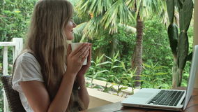 Woman with laptop computer on vacation in luxury resort. Woman with laptop and cup of coffee. Vacations concept stock video