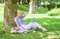 Woman with laptop computer work outdoors lean on tree trunk. Education technology and internet concept. Girl work with royalty free stock photography