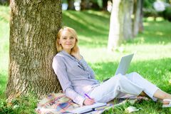 Woman with laptop computer work outdoors lean on tree trunk. Girl work with laptop in park sit on grass. Education stock images