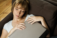 Woman with laptop on couch Royalty Free Stock Images