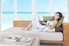 Woman with laptop on couch Royalty Free Stock Photos