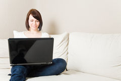 Woman with laptop on a couch royalty free stock image
