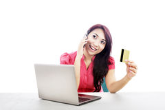 Woman with laptop and credit card. An attractive woman purchasing product online using her laptop computer, credit card, and mobile phone Stock Photos