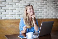 Woman with laptop and credit card in cafe . Online payment, digital banking. Young girl shopping stock images