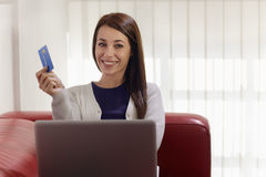 Woman with laptop and credit card shopping. E-commerce with happy woman using pc and credit card while shopping on the web at home Royalty Free Stock Photography
