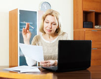 Woman with laptop and documents at table Royalty Free Stock Photos
