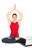 Woman with laptop doing yoga. Young woman performing yoga in front of a laptop Royalty Free Stock Photos
