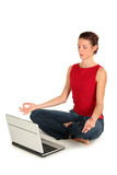 Woman with laptop doing yoga. Young woman performing yoga in front of a laptop Royalty Free Stock Image