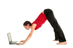Woman with laptop doing yoga. Woman doing yoga, downward dog position, side view Royalty Free Stock Image