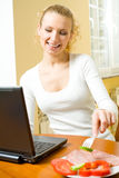 Woman with laptop, eating Stock Photo