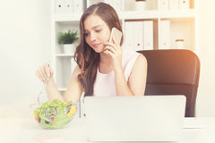 Woman with laptop eating salad in sunit office Stock Photo