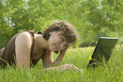 Woman with laptop in field Royalty Free Stock Photos