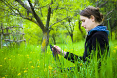 Woman with laptop in field Stock Photography
