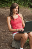 Woman with laptop in forest Royalty Free Stock Photography