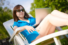 Woman with laptop and glass of martini outdoors Stock Photos