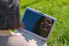 Woman with laptop on the grass Stock Photography
