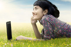 Woman with laptop on grass looking at sky Stock Photography