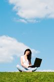 Woman with laptop on the green grass Stock Photos