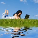 Woman with laptop on the green grass stock photo
