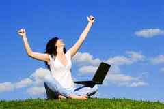 Woman with laptop on the green grass Stock Image
