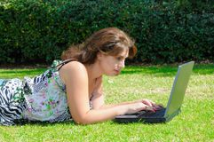 Woman with laptop on the green grass Royalty Free Stock Image