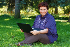 Woman with laptop on green lawn. Beautiful woman sitting cross-legged with her laptop on her lap on a green lawn Stock Photography