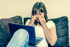 Woman with laptop having tired and sore eyes Stock Photography