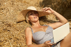 Woman on laptop in hay stack Royalty Free Stock Images