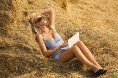 Woman on laptop in hay stack Stock Photos