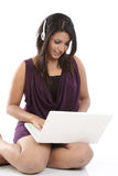 Woman with laptop and headphones Royalty Free Stock Photos