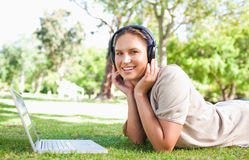 Woman with a laptop and headphones lying on the lawn Royalty Free Stock Photo