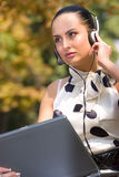 Woman with laptop and headset Royalty Free Stock Photos