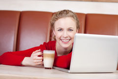 Woman With Laptop Holding Latte Cup In Coffee Shop. Portrait of happy young woman with laptop holding latte cup in coffee shop Royalty Free Stock Images