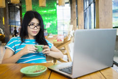 Woman with laptop and holds coffee Royalty Free Stock Image