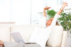 Woman with laptop at home. Smiling elderly woman with laptop at home stock images