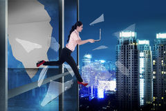 Woman with laptop jump through office building window Royalty Free Stock Image