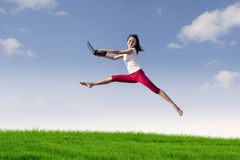 Woman with laptop jumping in meadow Stock Images