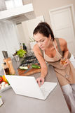 Woman with laptop in the kitchen Royalty Free Stock Photo