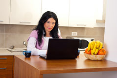 Woman with laptop in kitchen Royalty Free Stock Photography